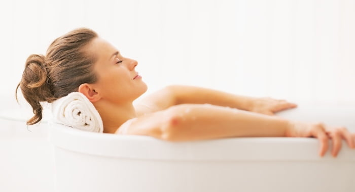 A warm bath is one of the good ways to relax your muscles before bed and ease the pain.
